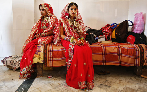 Brides sit after their make-up was done during a mass wedding ceremony at a temple in New Delhi