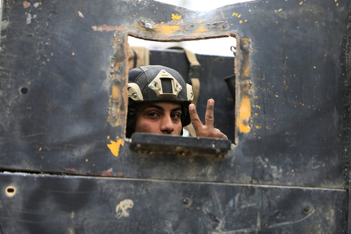 A member of the Iraqi Special Operations Forces (ISOF) gestures in military vehicle during a battle with Islamic State militants in Mosul
