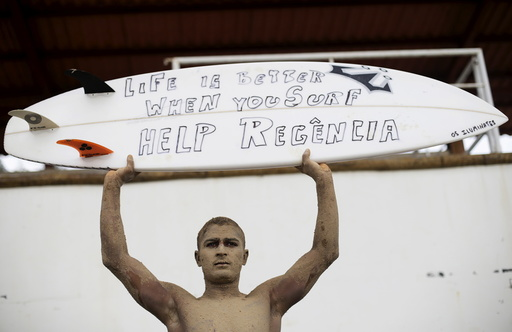 A surfer attends a protest in Regencia village, where, according to Brazil's environmental regulator IBAMA, the Rio Doce is about to be flooded with mud after a dam, owned by Vale SA and BHP Billiton Ltd burst, during a protest, Brazil