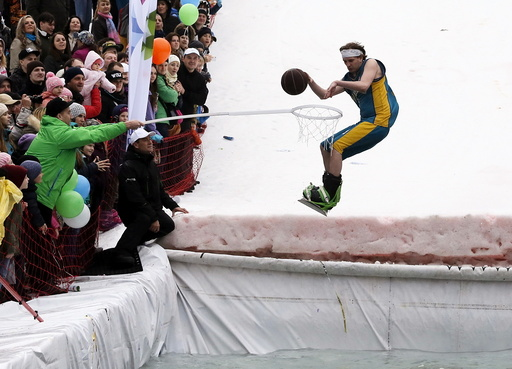 A snowboarder, wearing a costume of a basketball player, performs while attempting to cross a pool of water at the foot of a ski slope at the Bobrovy Log ski resort on the suburbs of the Siberian city of Krasnoyarsk