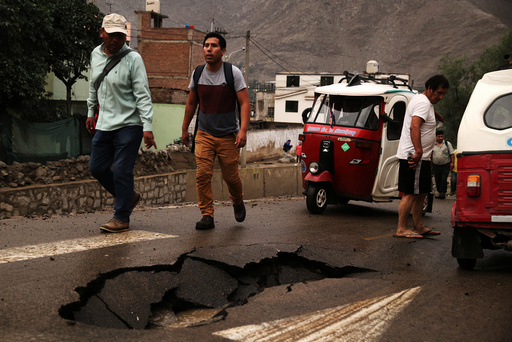 People walk after a landslide and flood in Chosica, east of Lima.