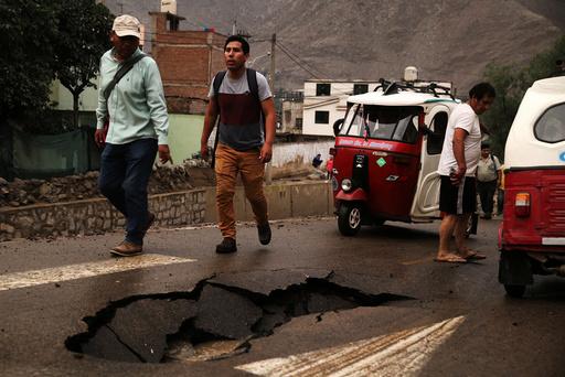 People walk after a landslide and flood in Chosica, east of Lima.
