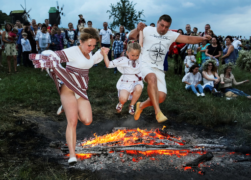 People jump over a campfire during a celebration on the traditional Ivana Kupala holiday in Kiev