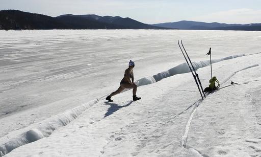 Woman wearing bikini exercises on bank of frozen Yenisei river in Taiga area south of Krasnoyarsk
