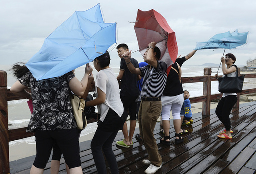 People hold onto their umbrellas as they encounter strong winds near the coast as Typhoon Utor hits Yangjiang