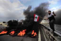 En demonstranter ved brennende bildekk som sperrer en av hovedveiene nord for Beirut. Foto: Hussein Malla / AP / NTB