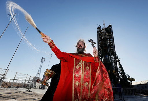 An Orthodox priest conducts a blessing in front of the Soyuz MS-04 spacecraft set on the launchpad at the Baikonur cosmodrome