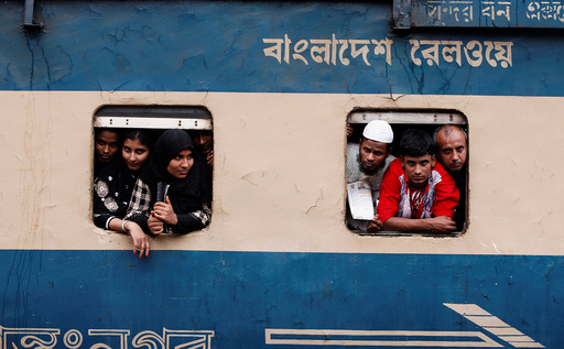 People stand in the windows of an overcrowded passenger train as they travel home to celebrate Eid al-Fitr festival, which marks the end of the Muslim holy fasting month of Ramadan, at a railway station in Dhaka