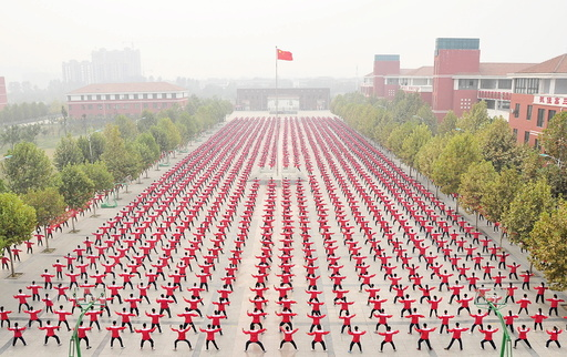 A Chinese national flag flies as students practice Taichi on a playground of a high school, during a Guinness World Record attempt of the largest martial arts display, on a hazy day in Jiaozuo