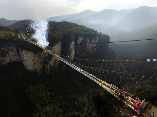 Fireworks go off to celebrate completion of construction of steel box girder on glass bridge as it suspends over canyon in Zhangjiajie National Park