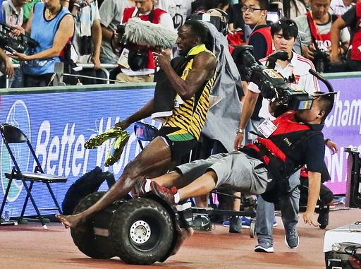 Usain Bolt of Jamaica is hit by a cameraman on a Segway as he celebrates winning the men's 200m final at the 15th IAAF World Championships in Beijing, China