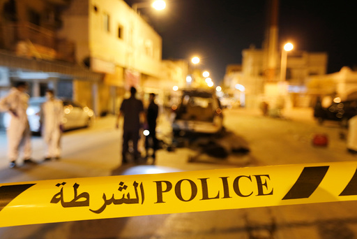 Police and crime scene officials are seen near scene where a blast killed one and seriously injured two police officers in the village of Diraz west of Manama